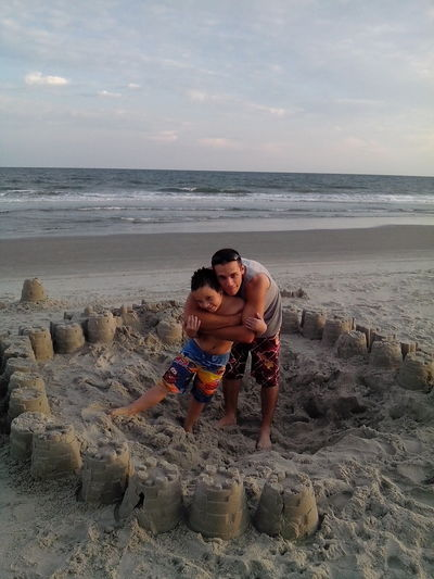 Full length of brothers standing on beach amidst sand castles against sky