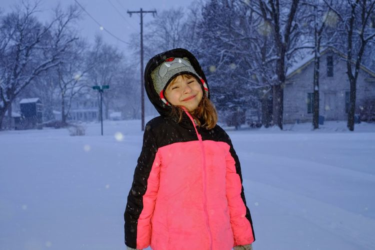 Portrait of smiling girl standing on field during snowfall