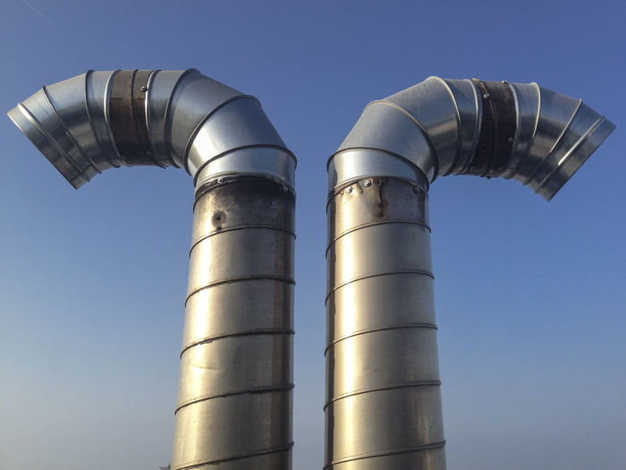 Curved steel pipes as smoke stack over blue sky Architecture Clear Sky Day Factory Industry Low Angle View Metal No People Outdoors Petrochemical Plant Sky