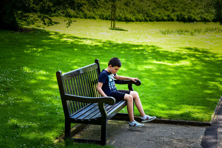 Side View Of Boy Sitting On Bench At Park