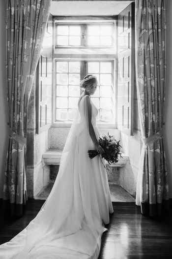 Full length of bride holding bouquet standing at home