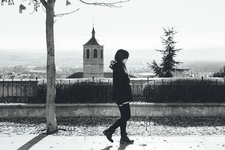 Side View Of Woman Walking On Footpath