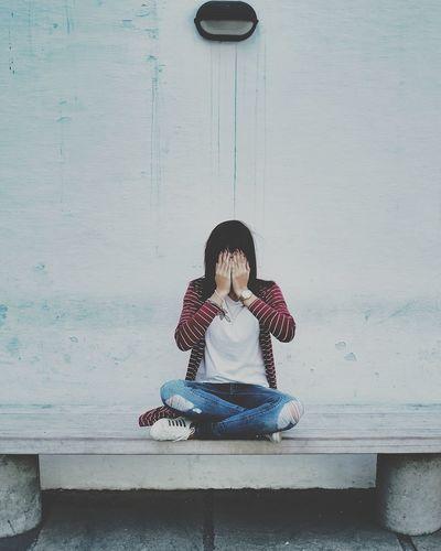 Woman sitting against wall