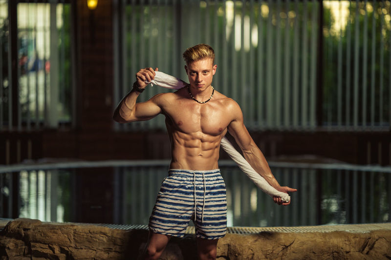 Portrait of shirtless muscular man standing by swimming pool