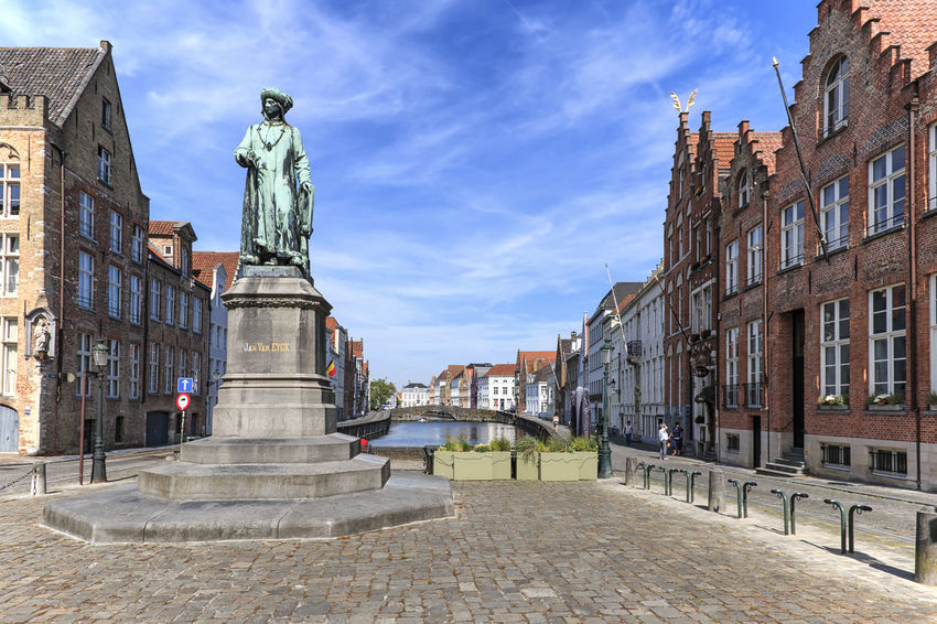 Bruges, Belgium - July 7, 2017: Panoramic view of the old streets of Bruges with a statue of Jan Van Eyck, a famous Flemish artist, on foreground Beer Belgium Brugge Chocolate Dijver Canal Duvel Flanders Panoramic View Provinciaal Hof West Flanders Aerial View Belfry Tower Bikes Bruges Europe Flower French Fries Holland Market Square Medieval Town Mussels