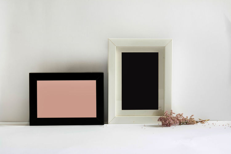 Close-Up Of Blank Picture Frames Against White Wall