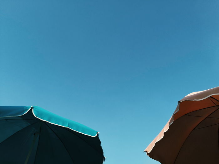 Low angle view of parasols against clear blue sky