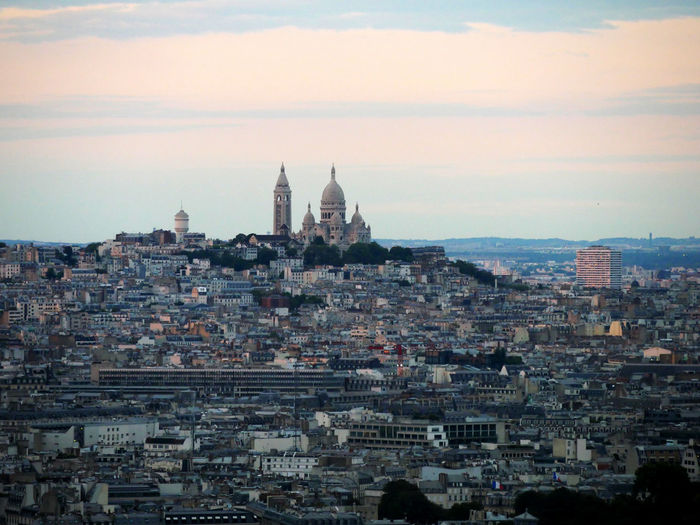 Mid distant view of basilique du sacre coeur against sky during sunset