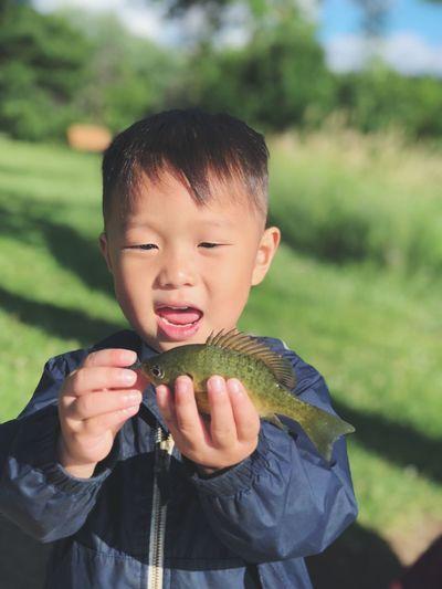 Boy holding dead fish on field