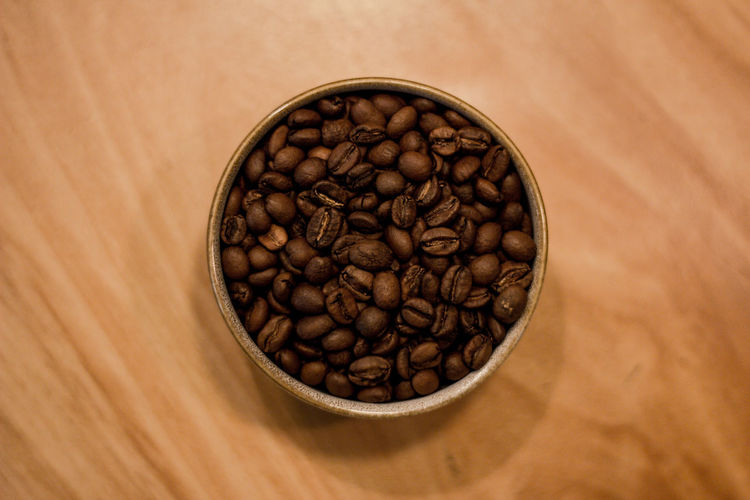 Food And Drink Coffee - Drink Brown Roasted Coffee Bean Coffee Table Freshness Indoors  Food Wood - Material Close-up Still Life Large Group Of Objects No People Abundance High Angle View Roasted Coffee Bean Directly Above Caffeine