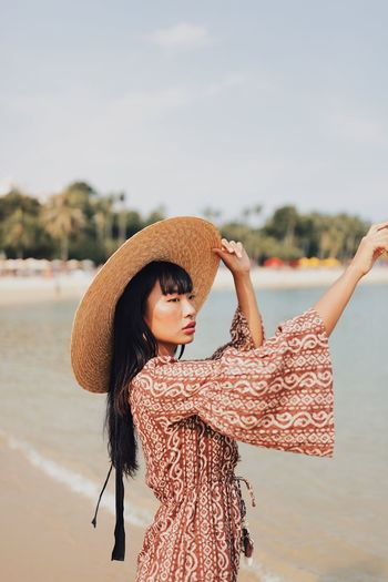 Young woman wearing hat looking away standing at beach against sky