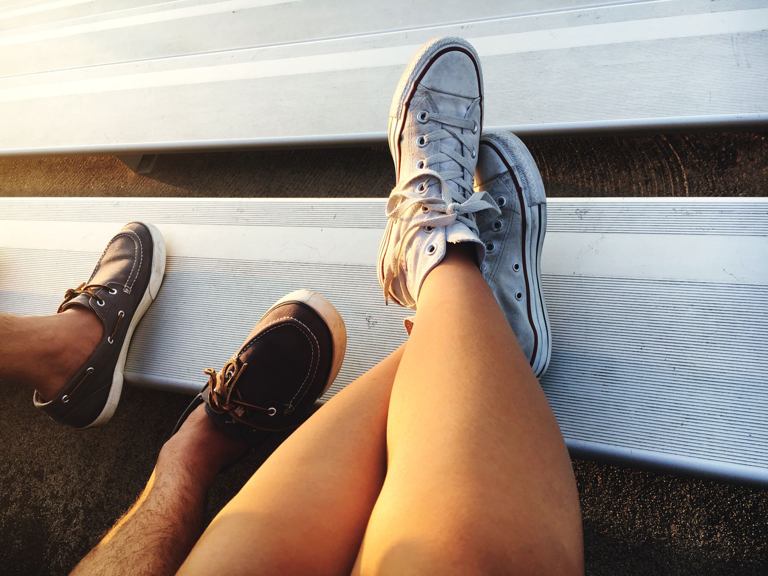 person, low section, personal perspective, shoe, sitting, relaxation, footwear, legs crossed at ankle, human foot, day