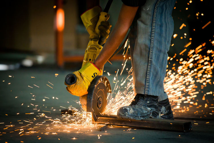 Low section of man working on metal at workshop