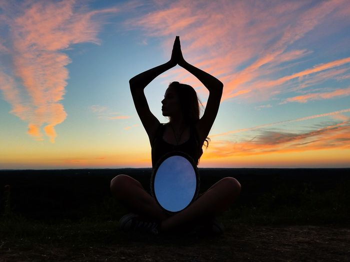 Woman With Arms Raised Against Sunset Sky
