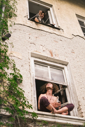 Hippie Window One Person Architecture Building Exterior Lifestyles Built Structure Day Young Adult Real People Plant Building Young Men Leisure Activity Portrait Low Angle View Men Nature Adult Outdoors