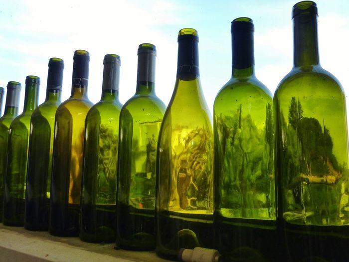 Close-up of empty wine bottles on window sill