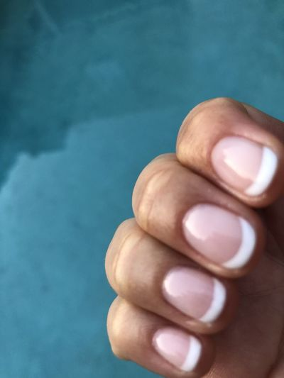 Cropped hand of woman against swimming pool