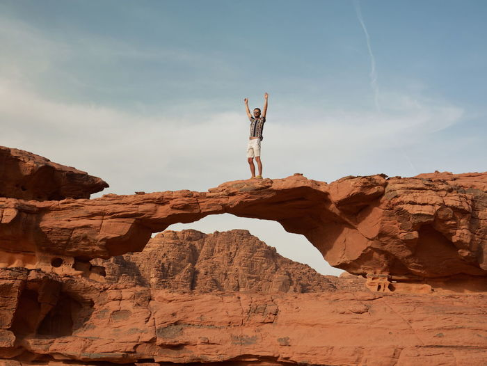 Young guy with hands in the air on rock formation in wadi rum desert