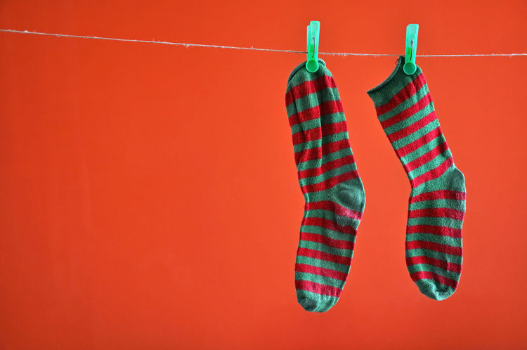 Pair of striped socks hanging on a rope isolated on red Clamp Clipped Close-up Clothesline Clothespins Clothing Coathanger Concept Footwear Hanging Home Hosier Lane Hosiery  Indoors  Laundry Line No People Nobody Red Red Background Rope Sock Striped Sock Tweezers Two Washing Line