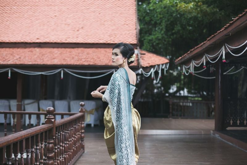 Side view of mid adult woman standing on walkway