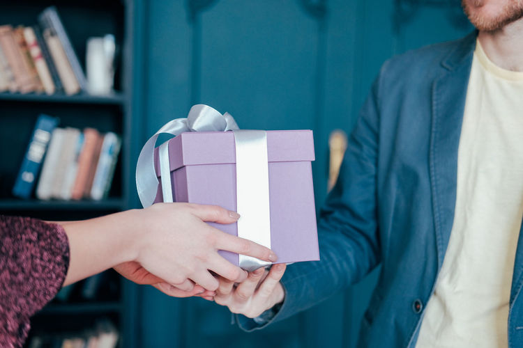 Midsection of woman holding hands in box