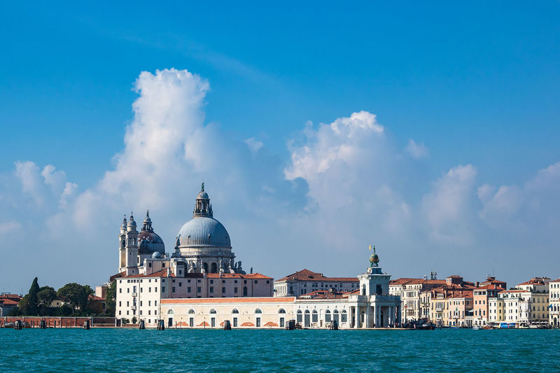 Grand canal with santa maria della salute in background against blue sky