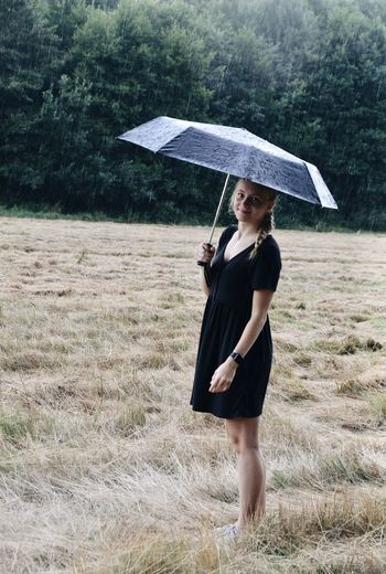 Full length of woman standing on field during rainy day