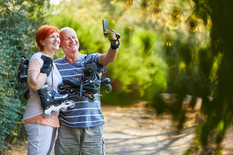 Smiling Couple Taking Selfie In Forest