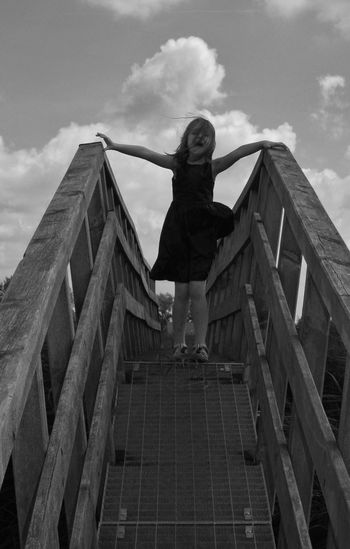 Low angle view of girl standing on footbridge against sky