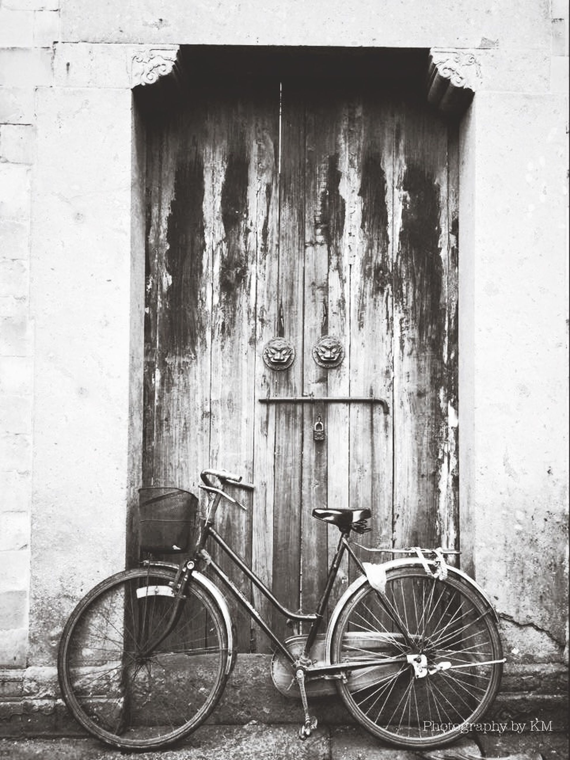 bicycle, building exterior, architecture, built structure, stationary, mode of transport, transportation, parked, door, land vehicle, parking, house, window, wall - building feature, closed, wall, day, outdoors, sidewalk, old-fashioned