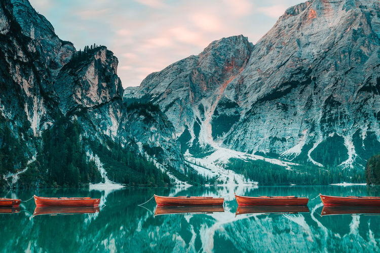 Scenic view of snowcapped mountains and rowling beats reflected in turqois lake at lago di braies