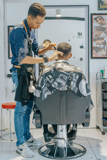 new cut, new style Indoors  Two People Men Real People Full Length Occupation Standing Males  Adult People Child Casual Clothing Boys Women Togetherness Care Barbershop Barber A New Beginning