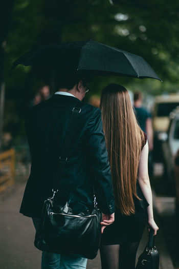 Rear view of couple walking on footpath during rain