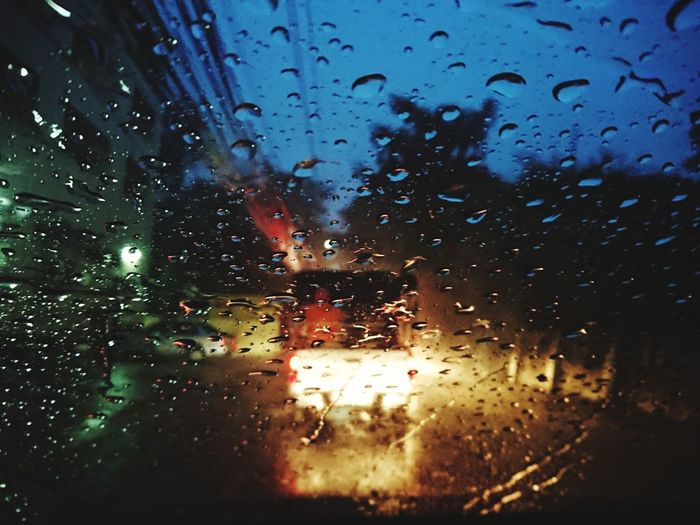 Cars on road seen through wet window during rainy season