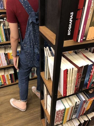 Low section of woman standing on shelf