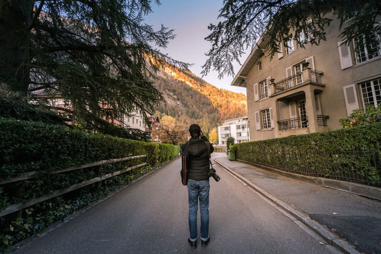 Rear view of man standing on road in city