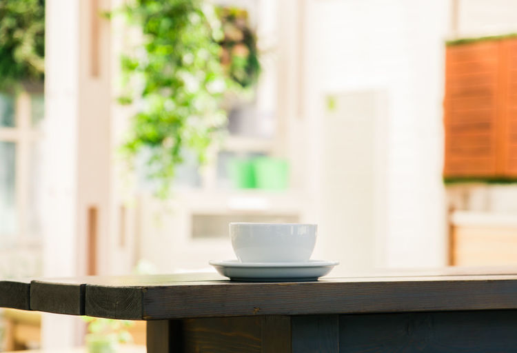 a Cup of coffee on the table in the cafe Cup Mug Drink Table Food And Drink Coffee Cup Indoors  Focus On Foreground No People Refreshment Saucer Coffee Day Wood - Material Coffee - Drink Crockery Window Home Interior Seat Tea Cup
