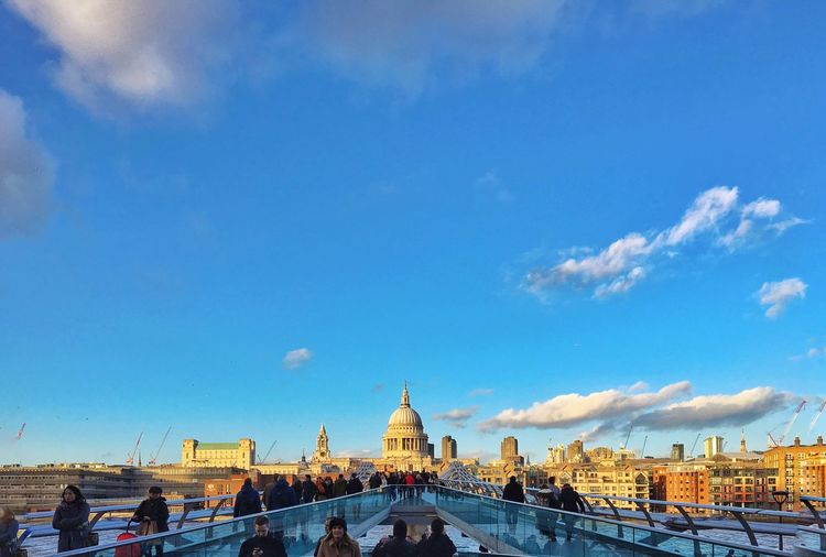 London millennium footbridge and st paul cathedral against blue sky in city