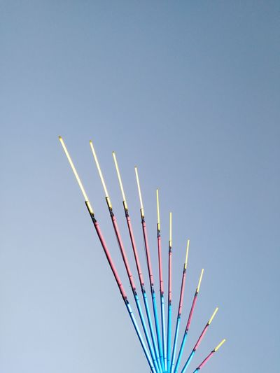 Low angle view of multi colored pencils against clear blue sky