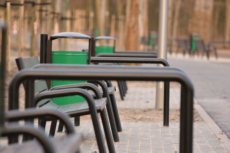 Benches and bicycle stands at the footpath Seat Empty Absence Day No People Metal Chair Bench Focus On Foreground Outdoors City Selective Focus In A Row Street Footpath Green Color Park Nature Park - Man Made Space Park Bench