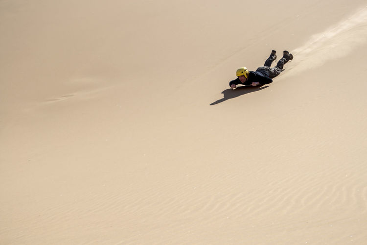 Man sliding down on a board, sandboarding, in the namibian dunes. copy space provided.