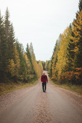 Rear view of woman walking on road amidst trees against sky