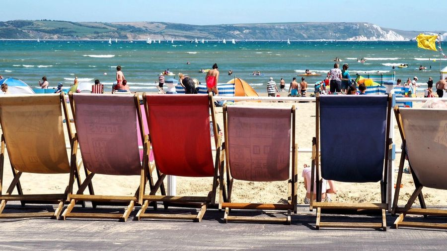 People Enjoying At Beach With Deck Chairs In Foreground