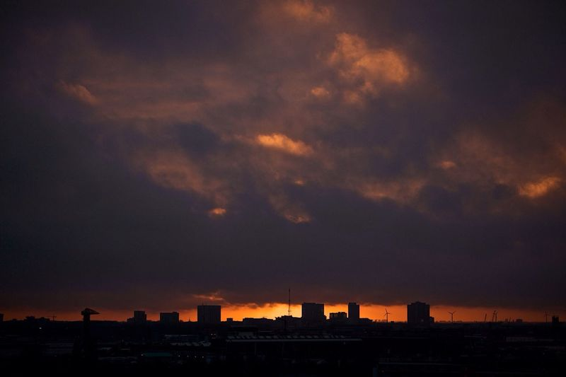Setting sun and dark clouds make a perfect skyline. Amsterdam Skyline Cityscapes