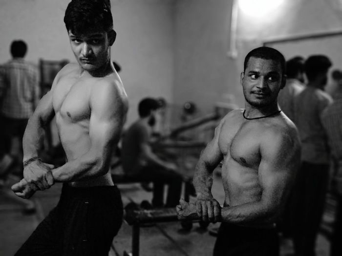 Shirtless Male Friends Flexing Muscles In Gym