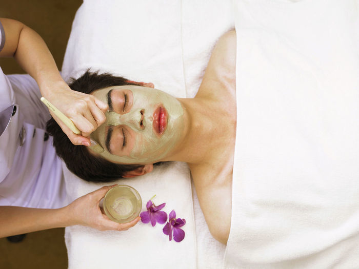 High angle view of massage therapist applying facial mask on man face