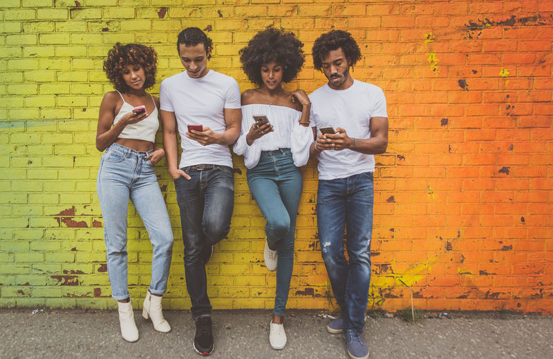 Group of friends with smartphones having fun together Togetherness Smile Modern Friendship Friends Phone Smart Phone Alienation Technology Application Message Text Digital Generation Millennials Teenager People Girls New York Colored Background Wall NYC American Row Urban