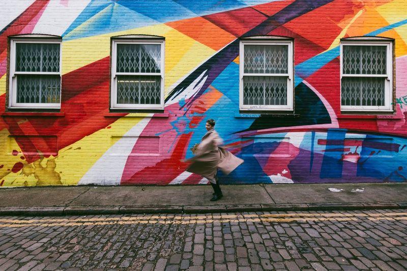 Woman walking on multi colored umbrella