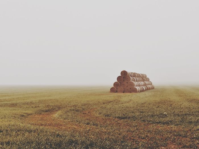 Stack of hay bales on grassy field against clear sky during foggy weather