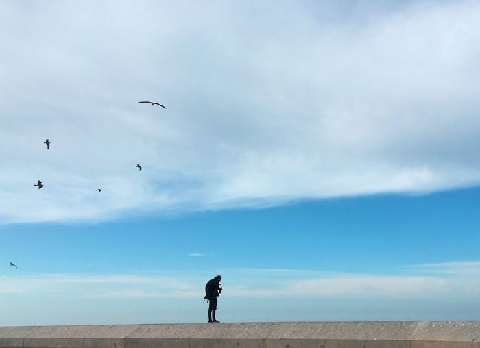 Man standing on railing against cloudy sky